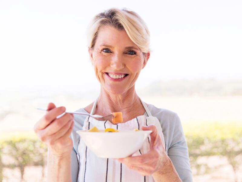 Donna over 50 mangia un'insalata di frutta